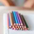 Colorful pencil crayons on spiral notebook — Stock Photo #54373611