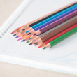 Closeup colorful pencil crayons on spiral notebook — Stock Photo #54375327