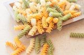Raw fusilli pasta på trä bricka — Stockfoto