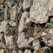 A volcanic stone and steel net fence texture background — Stock Photo #71464091