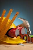 Yellow helmet and wooden mounting tools — Stock Photo