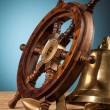 Anchor bell and old wooden steering wheel — Stock Photo #66222691