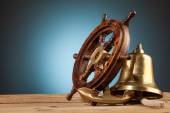 Anchor bell and old wooden steering wheel — Stock Photo