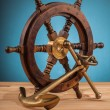 Old anchor and old steering wheel — Stock Photo #66617693