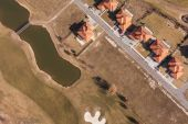 Aerial view over golf field and houses — ストック写真
