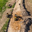 Aerial view of long arm excavator working on the field — Stock Photo #73809229