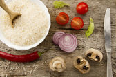 Cooking rice on aged wooden background. Cut onion, mushrooms. Chile pepper, cherry tomatoes, green salad. Healthy eating, diet, vegetarianism. — Stock Photo