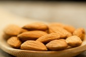 Peeled almonds in spoon on wooden background. For vegetarians — Stock Photo