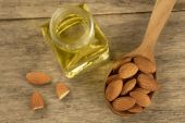 Peeled almonds in a spoon and oil in a jar on wooden background — Stock Photo
