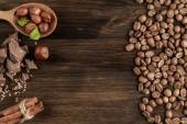 Chocolate bar, shelled hazelnuts, roasted coffee beans, cinnamon on wooden background, close up — Stock Photo
