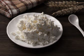 Fresh tasty curd in pot on wooden background. Homemade, cottage cheese — Stock Photo