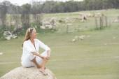 Happy relaxed woman outdoor sitting on rock — 图库照片