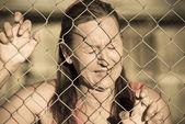 Devastatetd Crying woman at prison fence — Stock Photo
