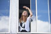 Concerned woman looking worried from window — Stock Photo