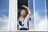 Woman looking up to sky from house window — Stock Photo