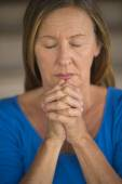 Mature Woman praying closed eyes folded hands — Stock Photo