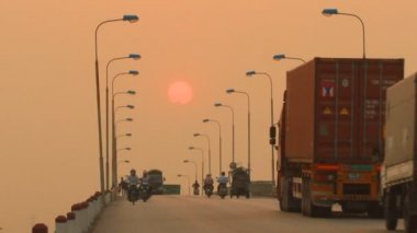 Haiduong, Vietnam, April, 21, 2015, Unidentified riders ride motorbikes on busy road at sunset — Stock Video