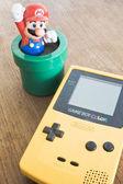 Game Boy Color device with Super Mario Bros figure — Stock Photo