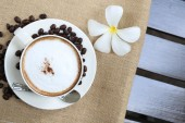 Cappuccino coffee cup and beans — Stock Photo