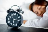 Asian woman sleeping on bed and wake up with alarm clock — Stock Photo