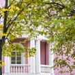 White balcony of pink house of classic style in autumn garden — Stock Photo #65638385