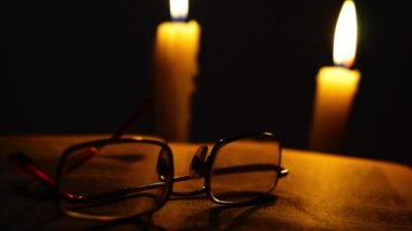 Old opened book and glasses in candles light — Stock Video
