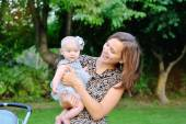 Smiling mother and baby playing in park  — Stock Photo