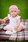 Baby girl in the park in a pink knitted hat — Stock Photo
