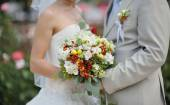 Bride holding wedding flower bouquet of white roses  — Stock Photo