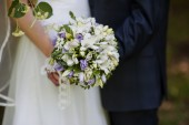 Wedding bouquet in hands of the bride and groom — Stock Photo