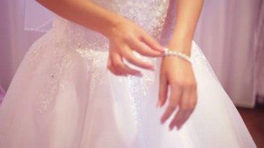Bride dresses bracelet on the arm — Stock Video