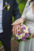 Hands of the bride and groom with wedding rings on a bouquet of  — Stock Photo