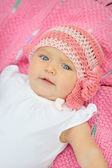 A cute little baby girl is staring up and is on a pink blanket — Stock Photo