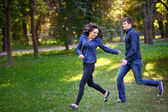 Couple in love in the park runs — Stock Photo