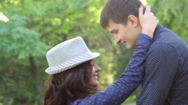 Girl in hat hugging a guy in the park — Vídeo Stock