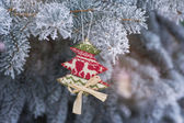 On a snowy tree branch hanging Christmas toy handmade — Stock Photo