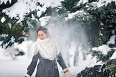 Snow flies on a girl in the park in winter with snow covered tre — Stock Photo