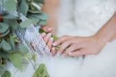 Hands of a bride, just married, a bridal bouquet is beside  — Stock Photo