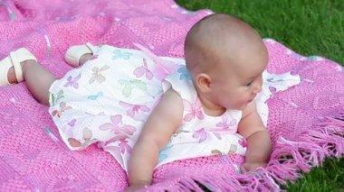 Heureux souriant joyeuse petite fille sur la couverture rose dans le parc — Vidéo