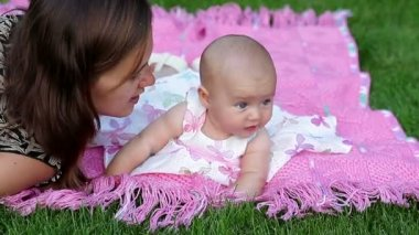 Happy smiling cheerful baby girl on pink blanket in park — Stock Video