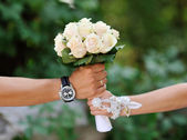 White wedding bouquet of roses in hands of the bride and groom.  — Stock Photo