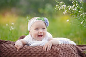 Baby smiling and looking up to camera outdoors in sunlight  — Stock Photo