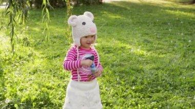 Little girl blowing soap bubbles, closeup portrait — Stock Video