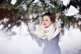 Winter girl blowing on a snowflake in knitted mittens — Stock Photo