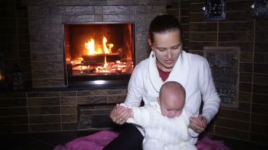 Mother sitting with her baby near the fireplace at Christmas — ストックビデオ