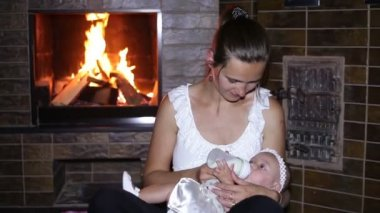 Mother feeds her baby near the fireplace — Stock Video