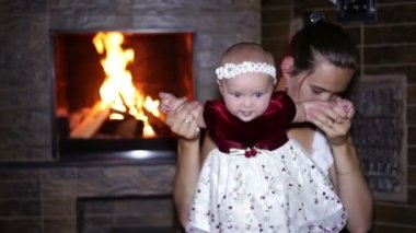 Mother sitting with her baby near the fireplace at Christmas — Stock Video