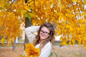 Beautiful young woman with yellow autumn wreath on bright backgr — Stock Photo