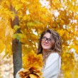 Young smiling girl-student in glasses close up against yellow au — Stock Photo #55619037