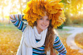 Young pretty woman in the autumn park makes a wreath of leaves — Stock Photo